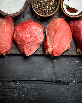 Raw meat. pieces of fresh beef with spices. on a black rustic.