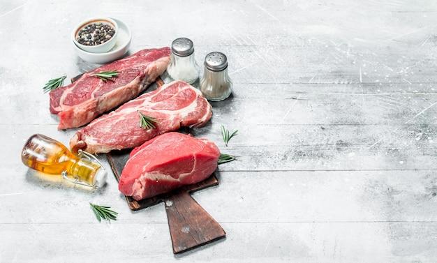 Сырое мясо. кусочки говядины и свинины со специями и зеленью. на деревенской поверхности.