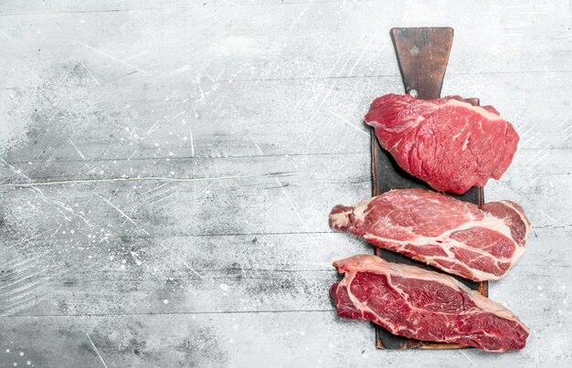 Сырое мясо. кусочки свинины и говядины на разделочной доске. на деревенском столе.