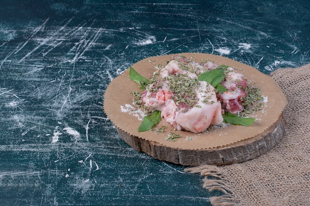 Raw meat pieces with fresh and dried herbs on blue.