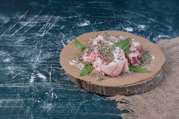 Pezzi di carne cruda con erbe fresche e secche sul blu.