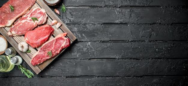 생고기. 향신료와 로즈마리 장식 트레이에 돼지 고기와 쇠고기 스테이크. 검은 소박한 배경.