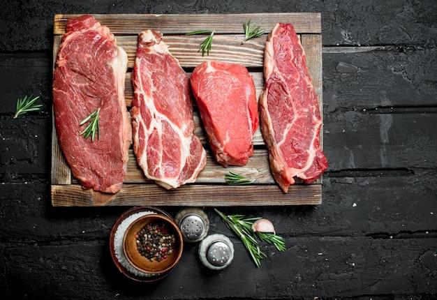 Сырое мясо. стейки из свинины и говядины на подносе со специями и веточкой розмарина. на черной деревенской поверхности.