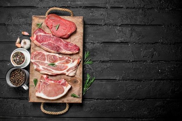 Сырое мясо. стейки из свинины и говядины на подносе со специями и веточкой розмарина. на черном деревенском столе.