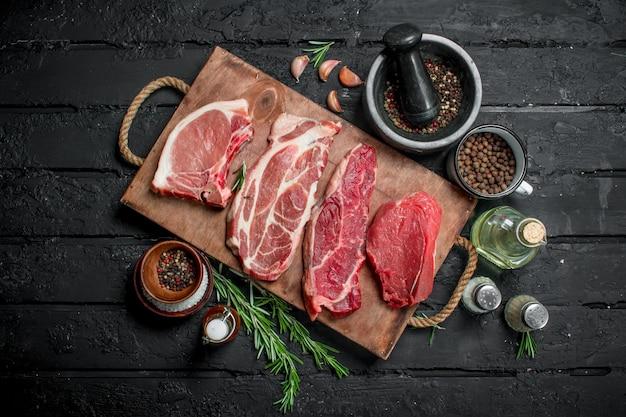 생고기. 향신료와 로즈마리 장식 트레이에 돼지 고기와 쇠고기 스테이크. 블랙 소박한에.