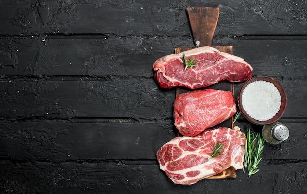 Сырое мясо. стейки из свинины и говядины с солью и специями. на черном деревенском фоне.