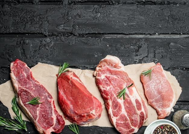 Сырое мясо. стейки из свинины и говядины со специями и зеленью. на черной деревенской поверхности.
