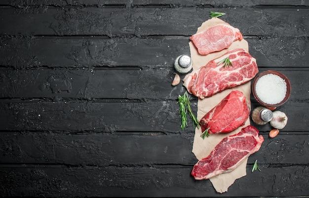 Сырое мясо. стейки из свинины и говядины со специями и зеленью. на черном деревенском столе.