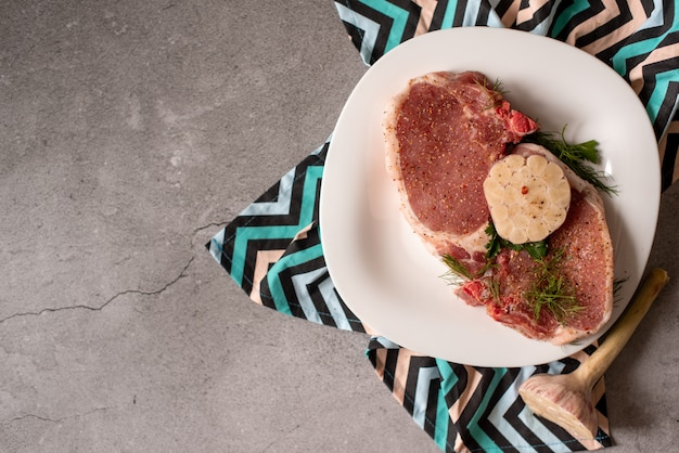 Raw meat. pork steak with dill in a plate