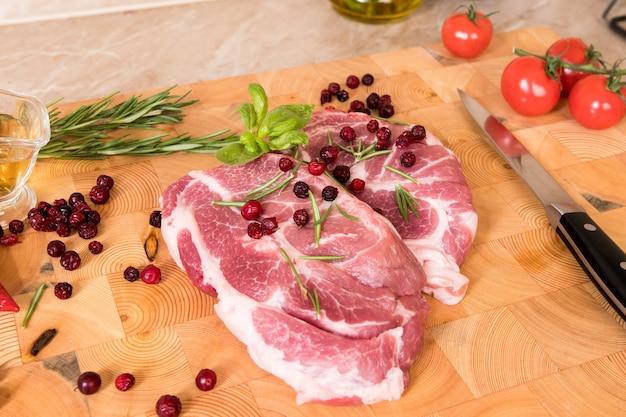 Сырое мясо. стейки из свинины на деревянной доске со специями, ягодами, маслом и помидорами черри, готовые для гриля и барбекю
