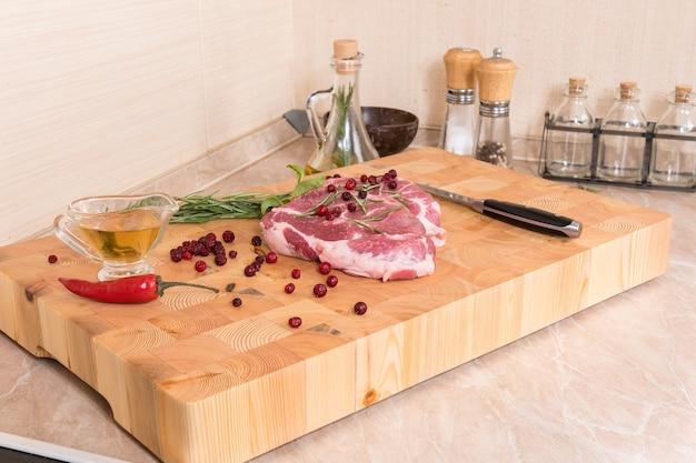 생고기. 향신료, 베리, 기름으로 나무 보드에 돼지 고기 스테이크
