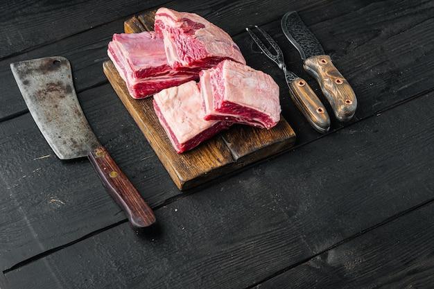 원시 고기 갈비 세트 및 텍스트 복사 공간이 검은 나무 테이블 배경에 오래 된 정육점 칼,