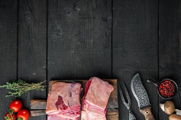 검은 나무 테이블 배경에 재료와 오래 된 정육점 식 칼 세트, 원시 고기 갈비, 상위 뷰 평면 누워, 텍스트 복사 공간