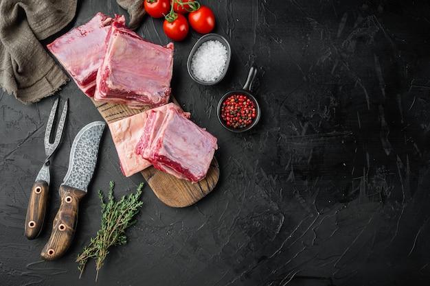 검은 돌 배경에 재료와 함께 원시 고기 갈비 세트, 평면도 평면 누워, 텍스트 복사 공간