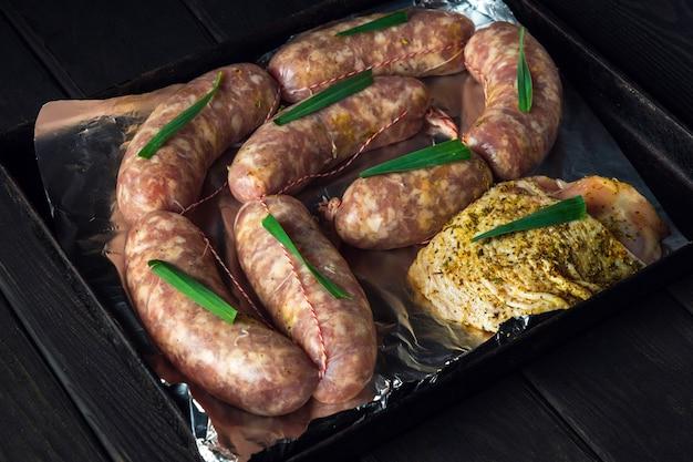 오븐에서 굽기 위해 시트 팬에 생고기 소시지와 햄을 준비합니다. 국가 고기 요리는 휴일 전에 준비됩니다.