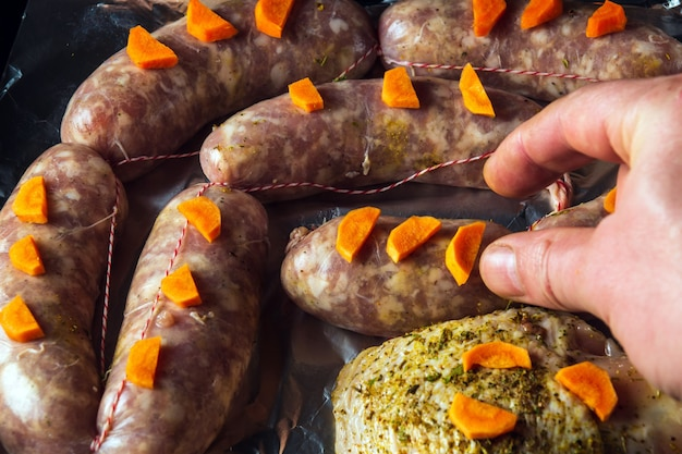 시트 팬에 당근과 햄을 넣은 생고기 소시지는 오븐에서 굽기 위해 준비됩니다. 국가 고기 요리는 휴일 전에 준비됩니다.