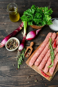 Raw meat sausages for barbecue or hot dog. purple onions, salt and pepper, fresh oregano for marinade. grill  family dinner
