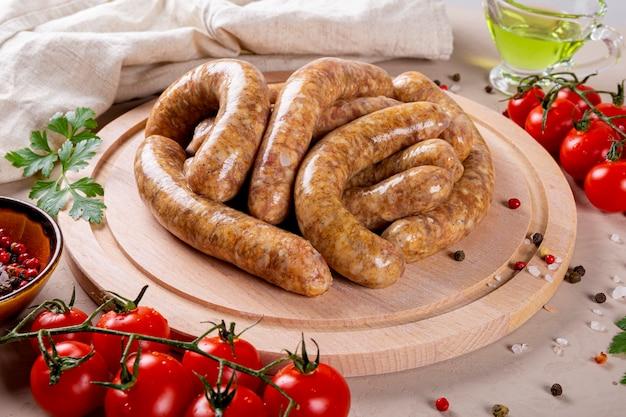 둥근 나무 커팅 보드에 쇠고기와 다진 돼지 고기의 생고기 소시지와 그것을 요리하기위한 제품이 닫힙니다.