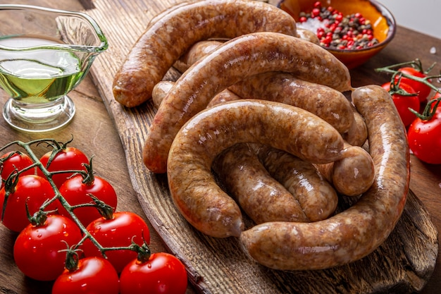 나무 커팅 보드에 쇠고기와 다진 돼지 고기의 생고기 소시지와 그것을 요리하는 제품을 닫습니다.