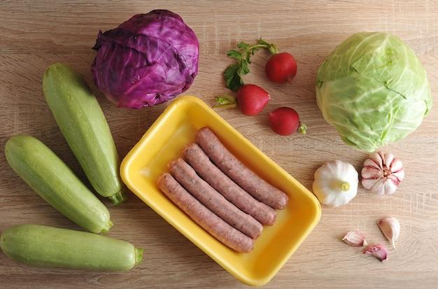 Сырые мясные колбаски купаты и овощи