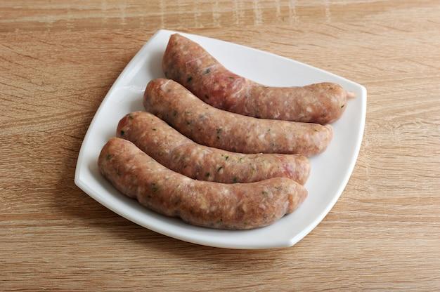 Сырые мясные колбаски купаты в белой тарелке