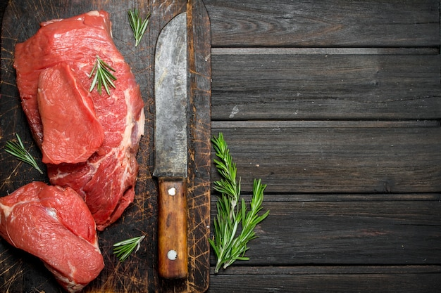 Raw meat. sliced beef with rosemary and old hatchet on a wooden table.