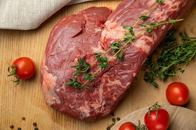 나무 보드에 향신료와 허브와 함께 쇠고기의 생고기 슬라이스 조각