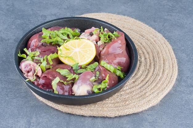 Ломтики сырого мяса и нарезанный лимон на черной тарелке.