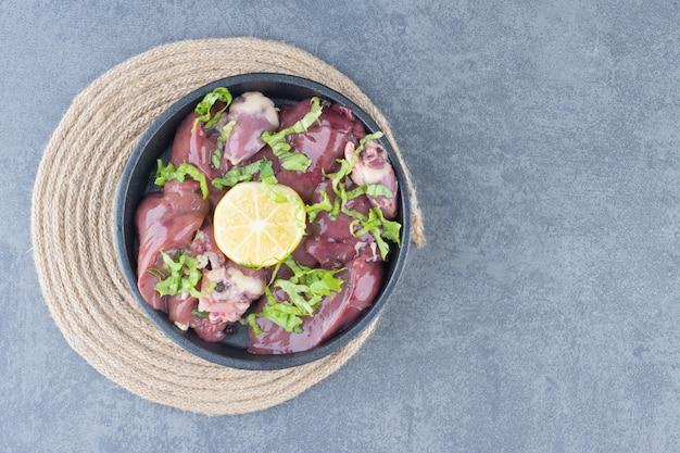 Fette di carne cruda e limone a fette sulla banda nera. Foto Gratuite