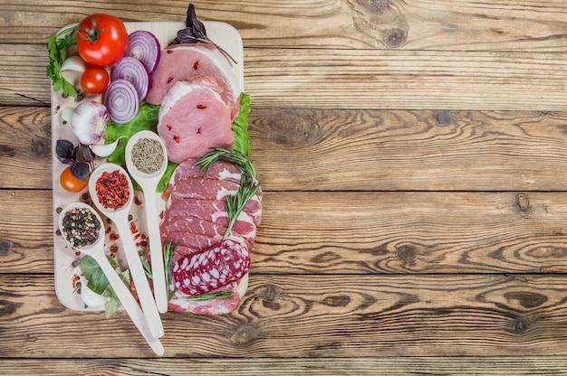 Сырое мясо, специи и колбасы на деревенской деревянной доске
