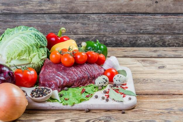 Сырое мясо, специи и овощи на деревенской деревянной доске