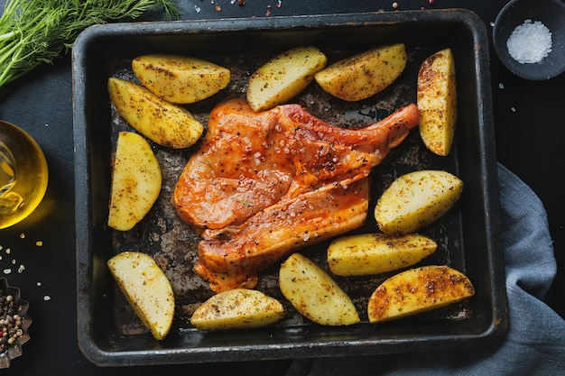 Стейк из сырого мяса из свинины с сырым картофелем и специями на стали духовки на темном фоне. вид сверху
