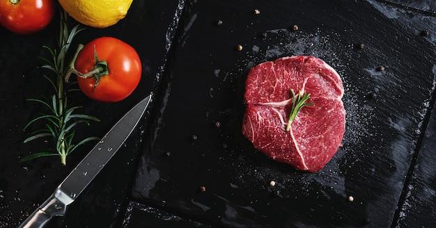 生の肉ステーキテンダーロインフィレ、黒い石のプレートで野菜