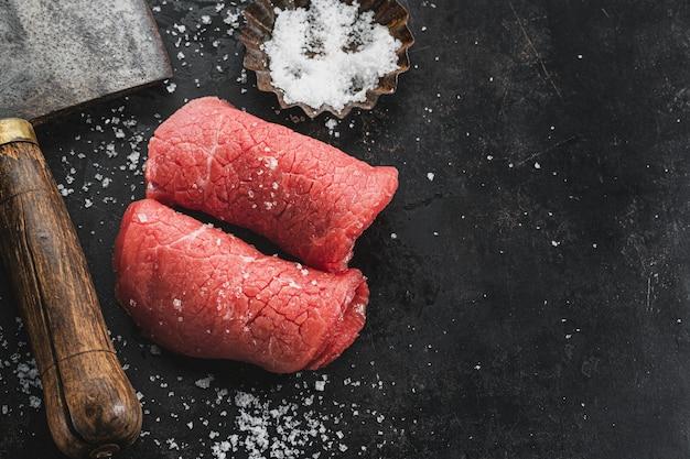 Стейк из сырого мяса с солью и ножом мясников на темном винтажном фоне. крупный план.