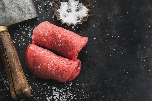 Raw meat steak with salt and butchers knife on dark vintage background. closeup.