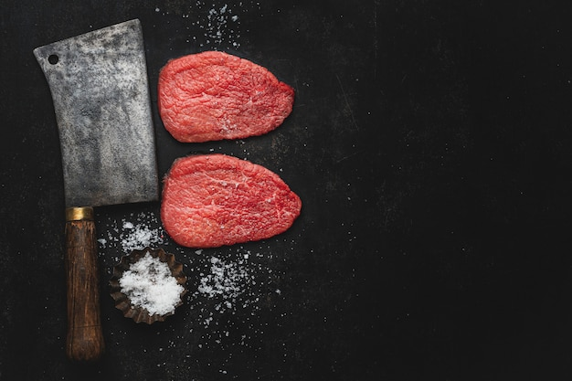 Raw meat steak with salt and butchers knife on dark vintage background. view from above.