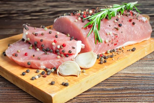 커팅 보드에 향신료와 생고기 스테이크. 돼지 고기, 로즈마리, 후추, 향신료, 마늘 나무 배경