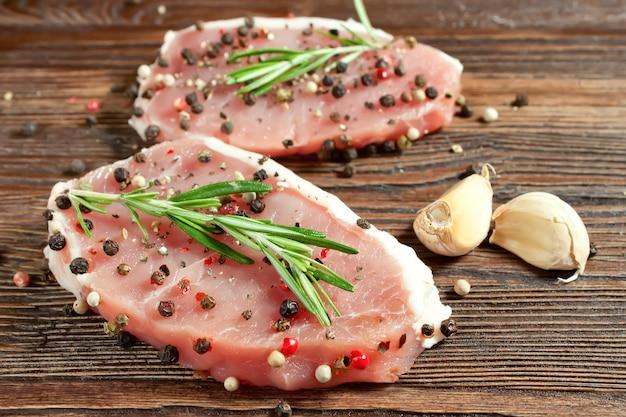 갈색 나무 보드에 향신료와 생고기 스테이크. 돼지 고기, 로즈마리, 후추, 향신료, 마늘 나무 배경