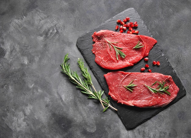 Raw meat steaks on black surface with brunches of rosemary and pomegranate seeds
