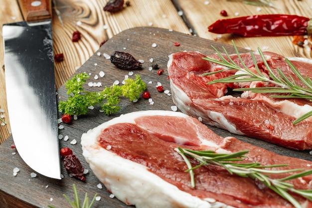 Стейки из сырого мяса с зеленью на деревянной доске