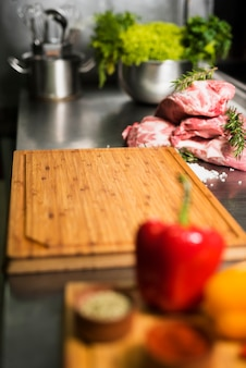 Raw meat steaks with wooden board on table