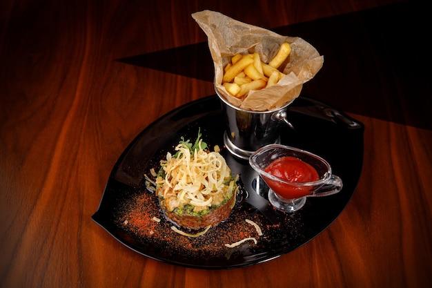 Тартар из сырого мяса с луком, картофелем фри и соусом на темной тарелке.