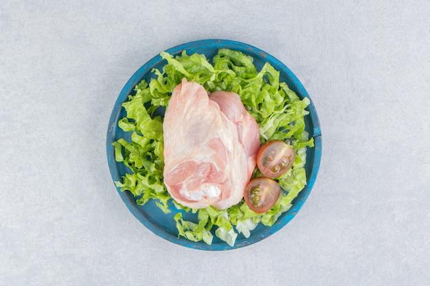 Сырое мясо, помидоры и зелень в тарелке на мраморной поверхности