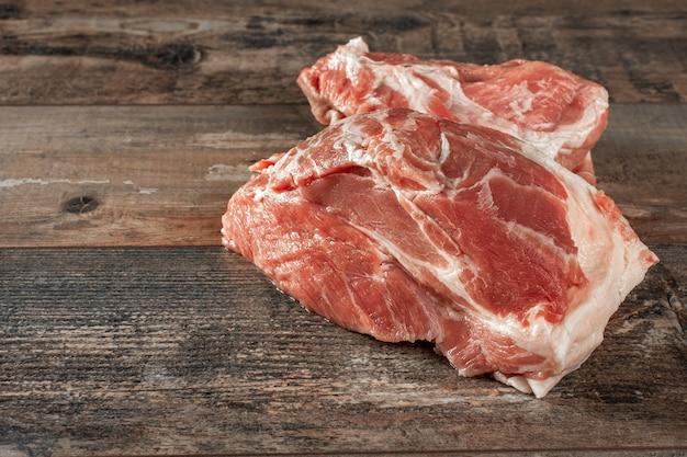 Сырое мясо. два куска сырой свинины на деревянном деревенском столе