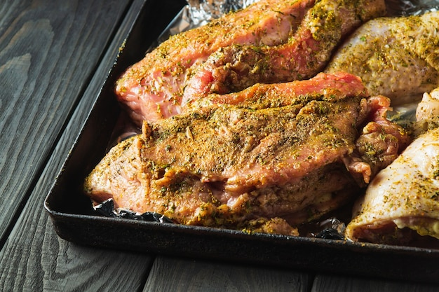 オーブンで焼くために、ベーキングシート上の生肉の子牛肉と鶏の脚を用意します。国民の肉料理は休日の前夜に用意されます。