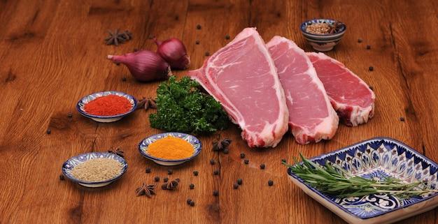 니스 칠한 보드에 허브와 양상추, 양파를 곁들인 생고기