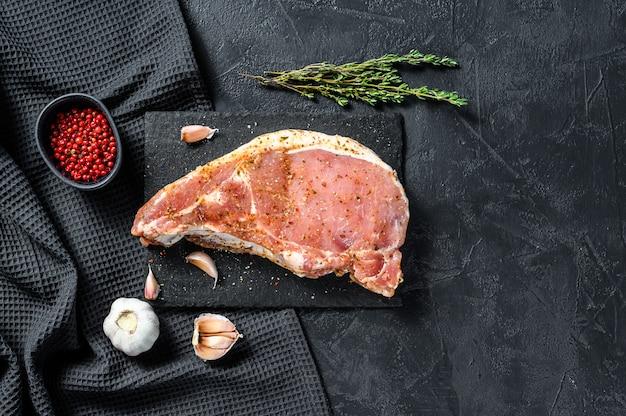 허브와 향신료와 생고기. 절인 돼지 고기 스테이크. 요리 재료. 검정색 배경. 평면도