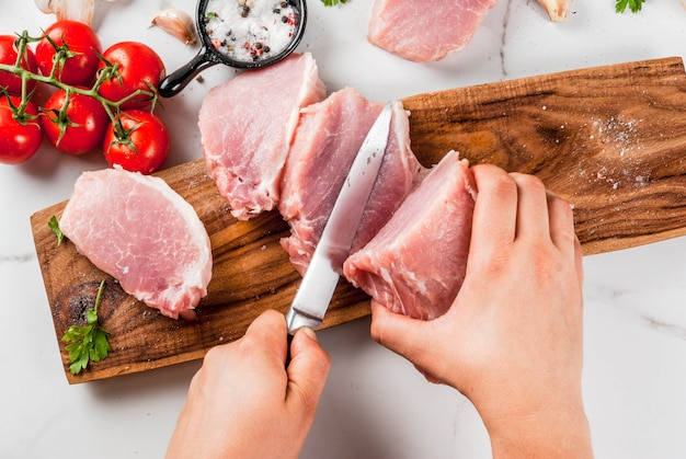 Raw meat with ingredients for dinner. person cut out pork fillet, tenderloin, on cutting board, with salt, pepper, parsley, rosemary, oil, garlic, tomato, mushroom.black stone table, copy space