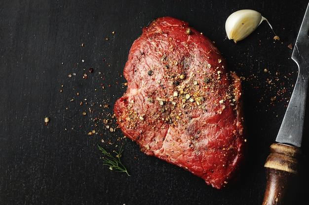 Сырое мясо со специями на темном столе. готов к приготовлению.