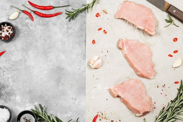 Сырое мясо с различными специями на сером фоне. вид сверху, скопируйте пространство. пищевой фон